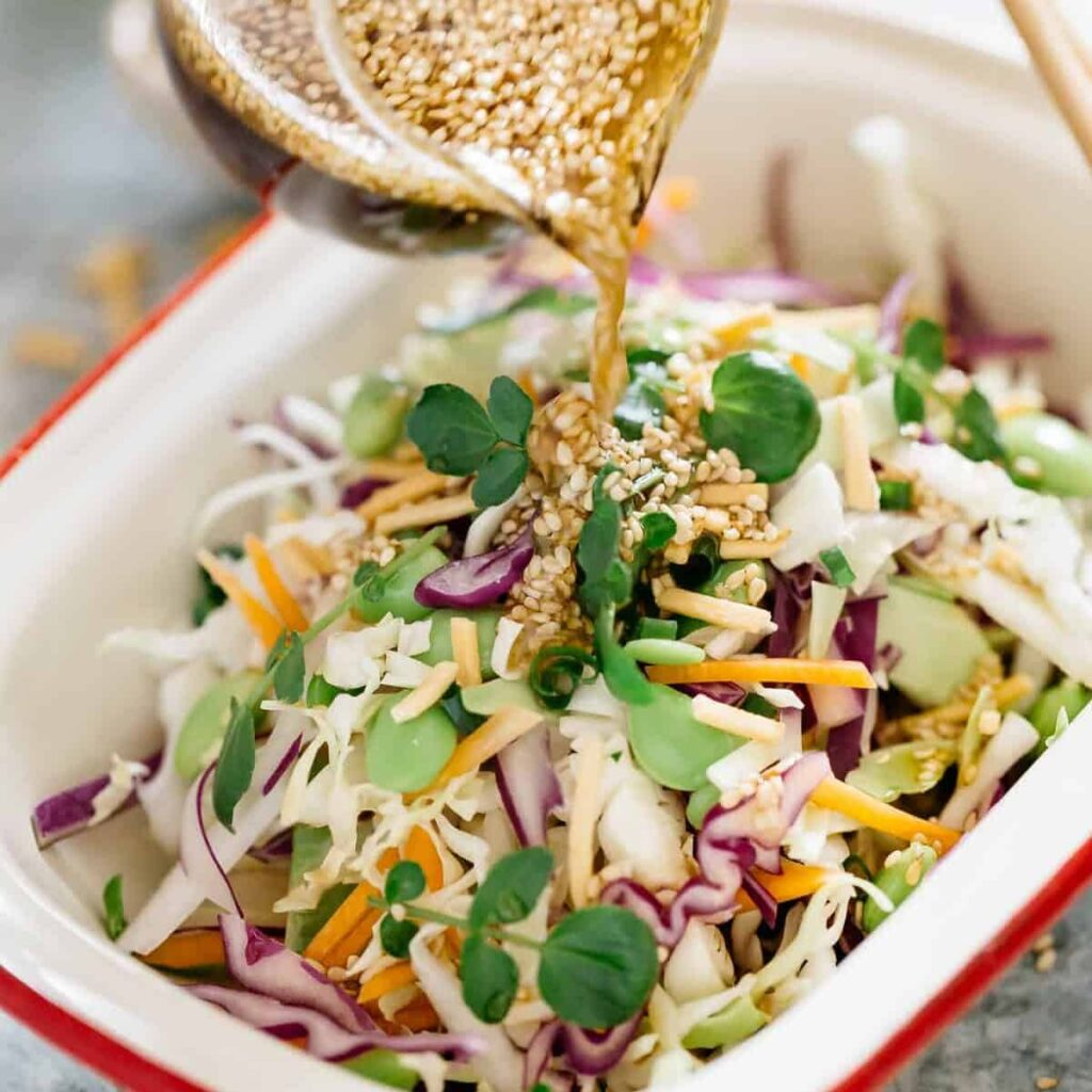 Asian Slaw in a rectangle dish. The sesame soy dressing being pored over.