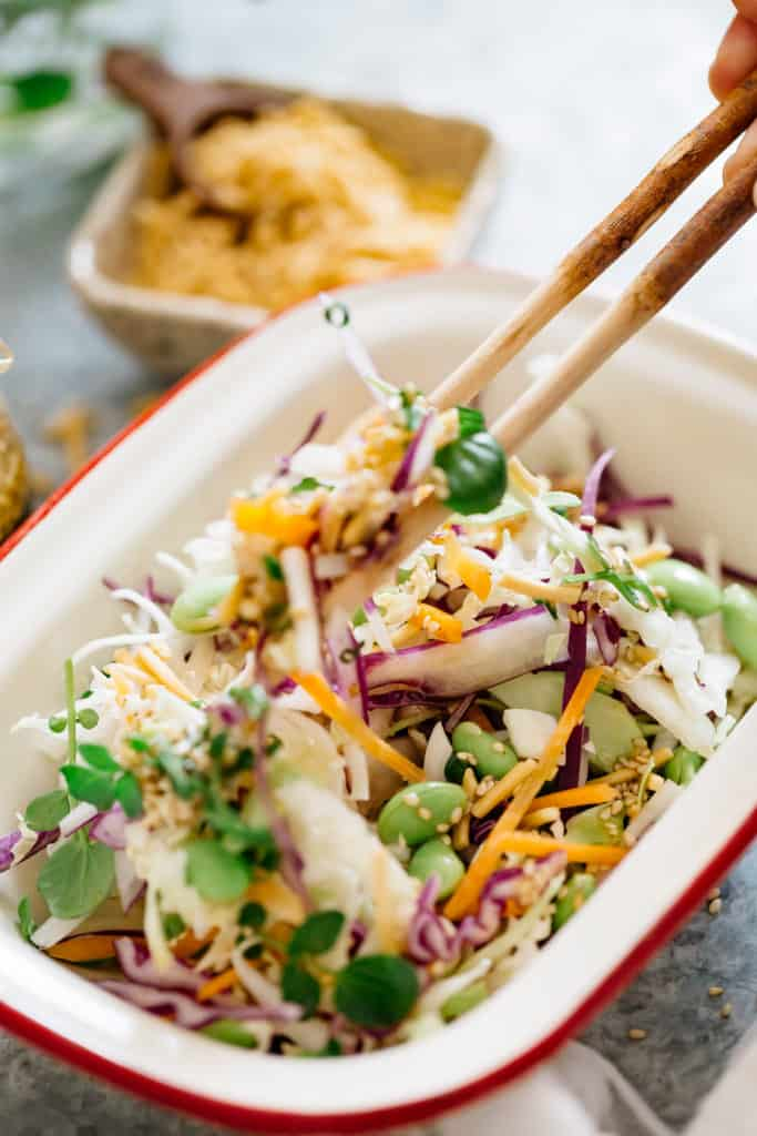a pair of chopsticks digging into the asian slaw salad
