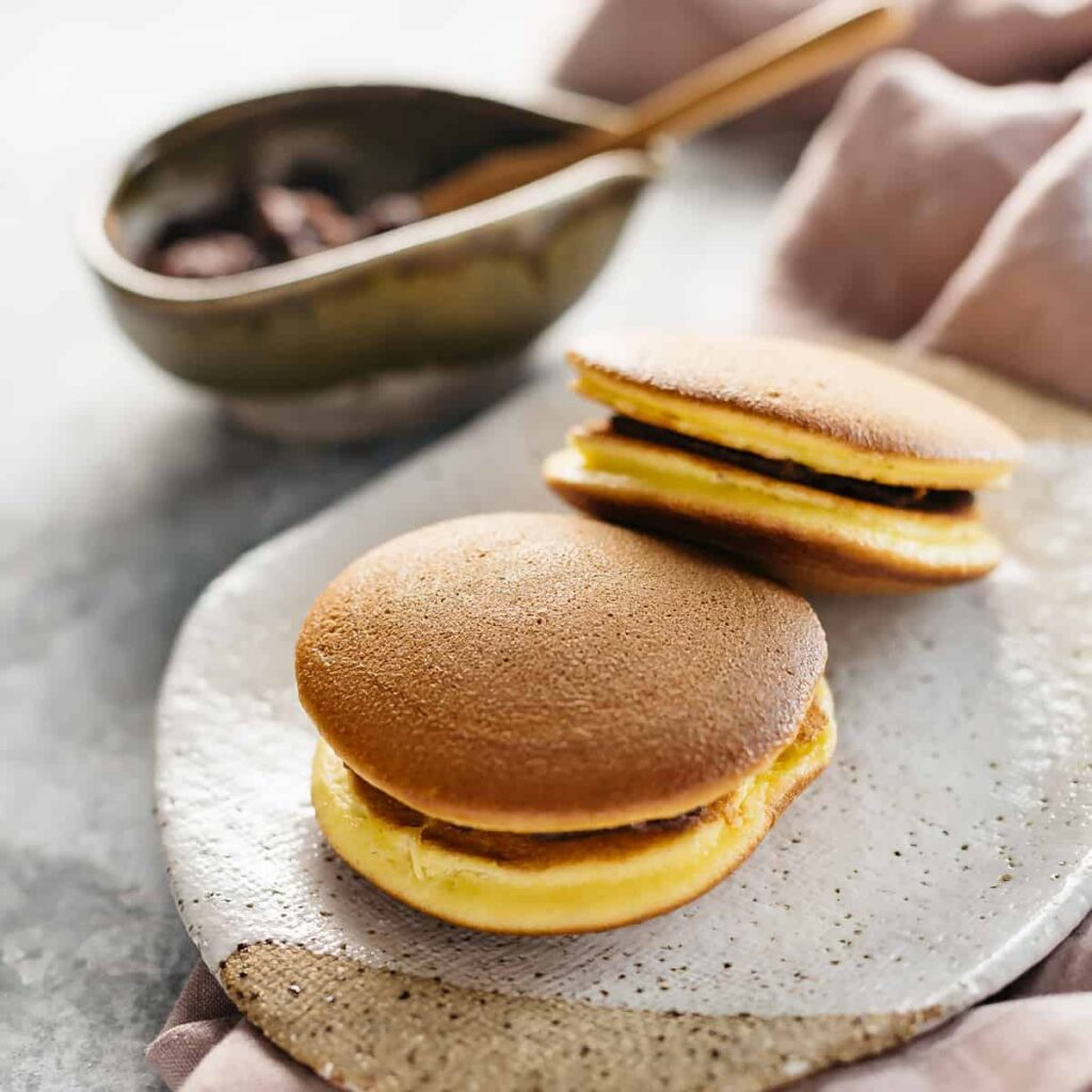two dorayaki on a plate with sweet azuki bean paste in a bowl in background