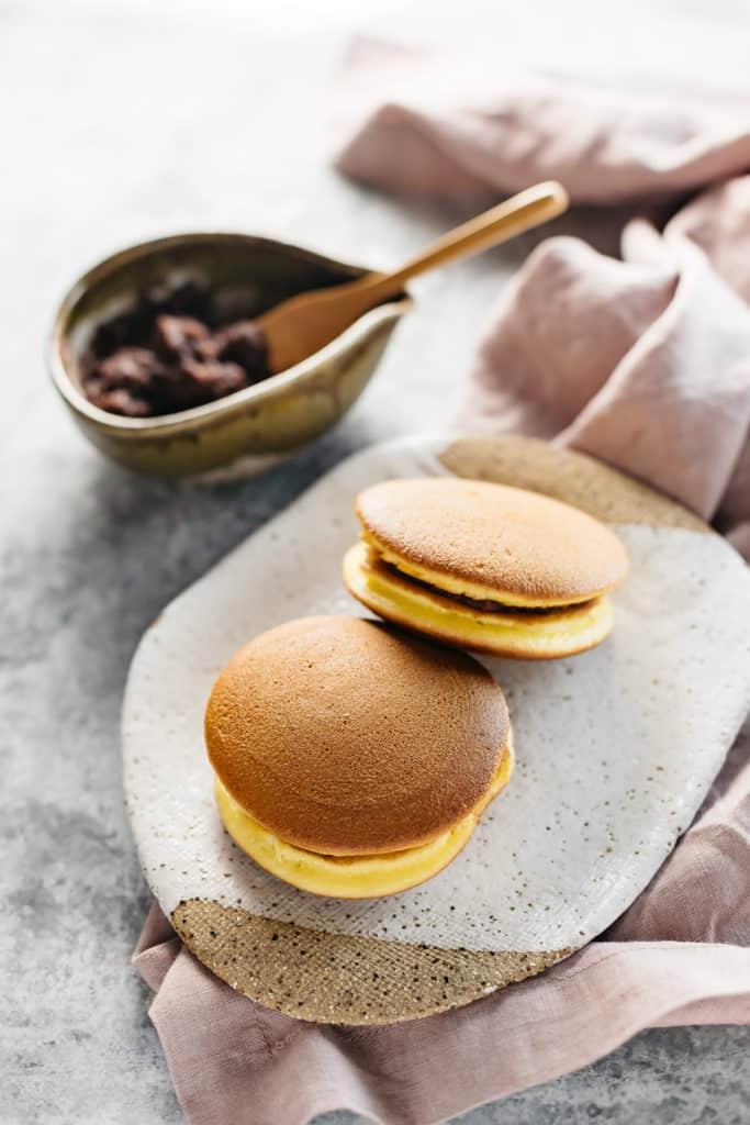 2 dorayaki on a plate with a bowl of sweet azuki bean paste