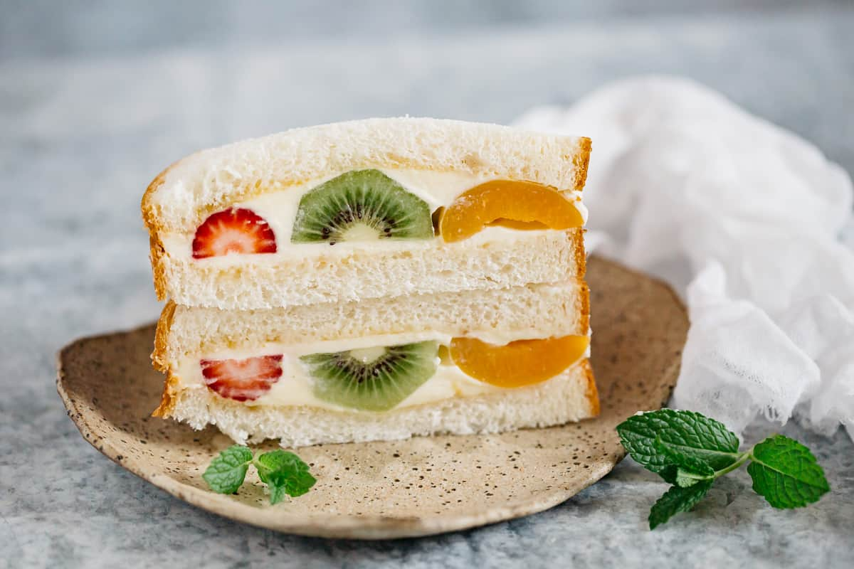 two pieces of fruit sandwich stacked up on a plate