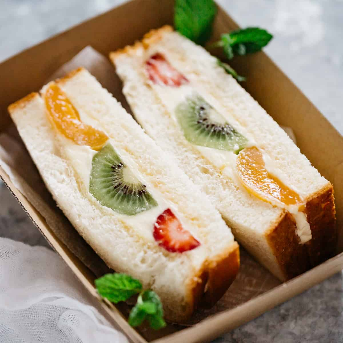 2 pieces of Fruit Sandwich in a takeaway cardboard container