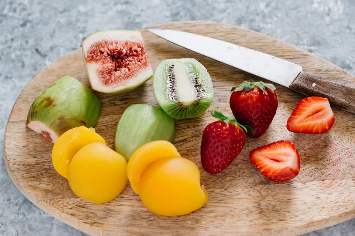 fig, kiwi fruit, strawberry, and apricots on a chopping board with a knife
