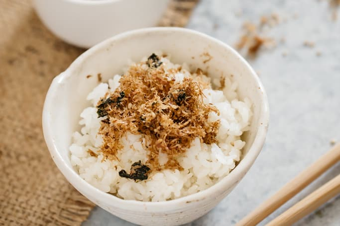 Furikake rice seasoning sprinkled over plain cooked rice in a rice bowl
