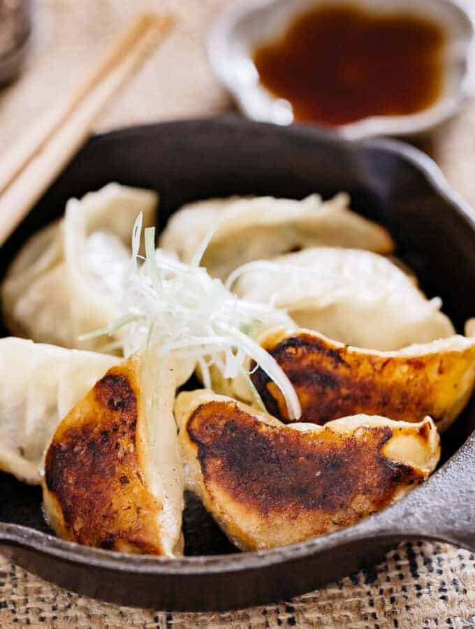6 gyoza pan fried in a cast iron skillet, three of them showing blackened bottom