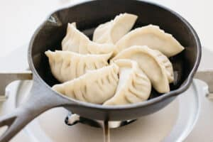 6 gyoza being fried in a cast iron skillet