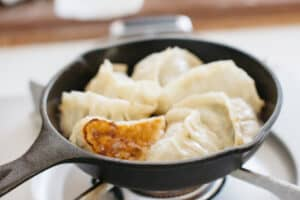 6 gyoza dumplings in a cast iron skillet