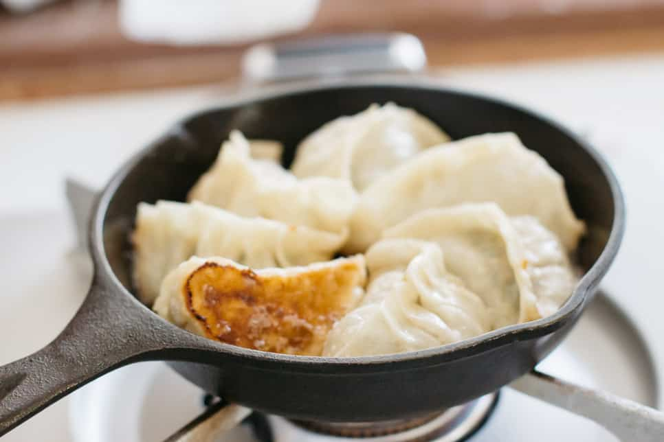 6 gyoza dumplings in a cast iron skillet