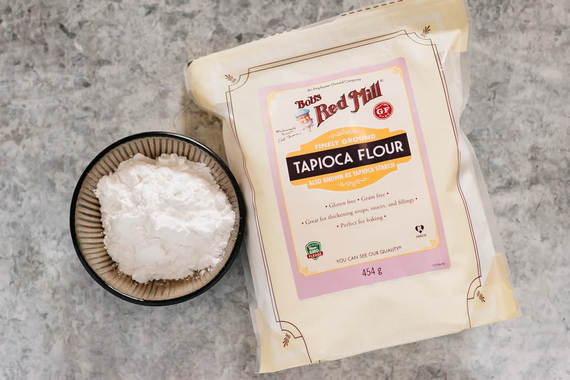 Tapioca starch in a small bowl and Bob's red mill brand tapioca starch packet on the right.