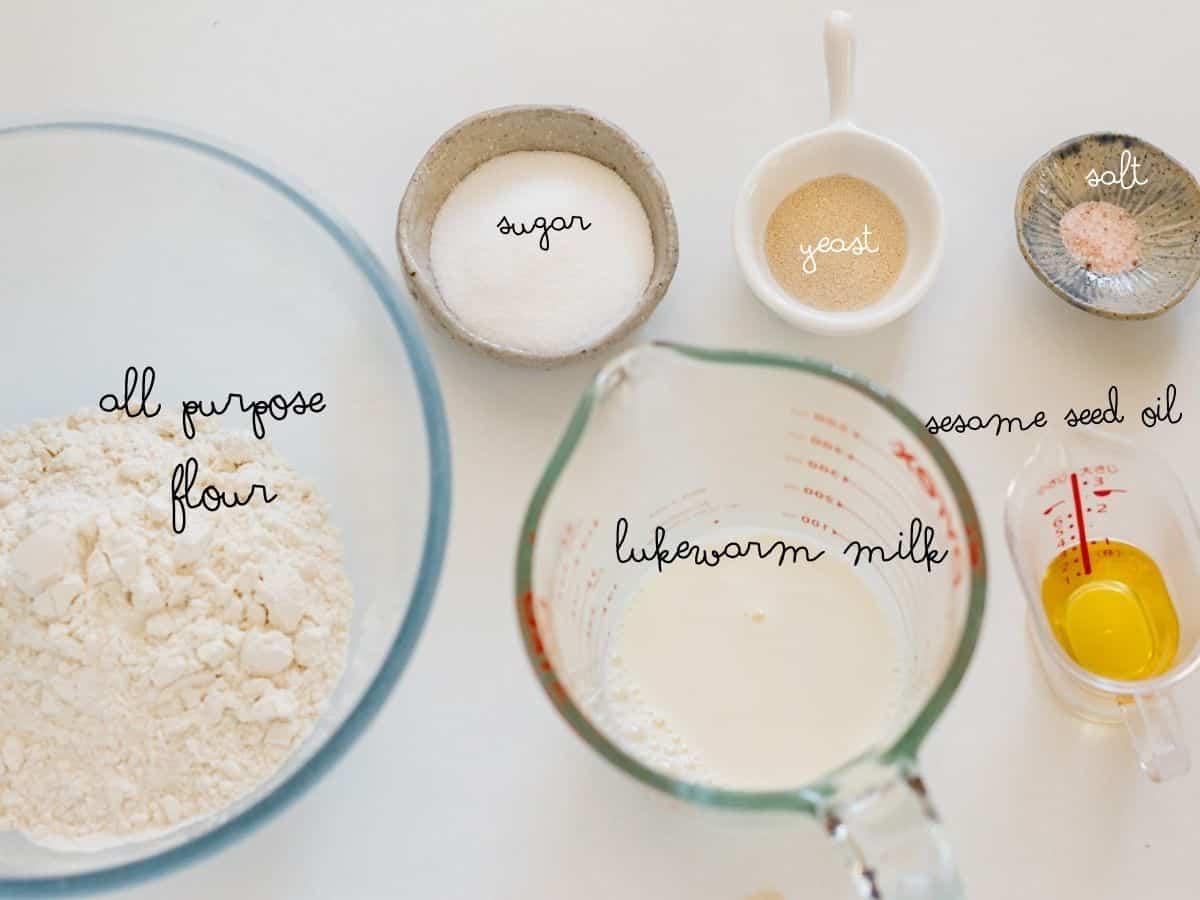 all purpose flour, sugar, lukewarm milk, instant dry yeast, salt and sesame seed oil