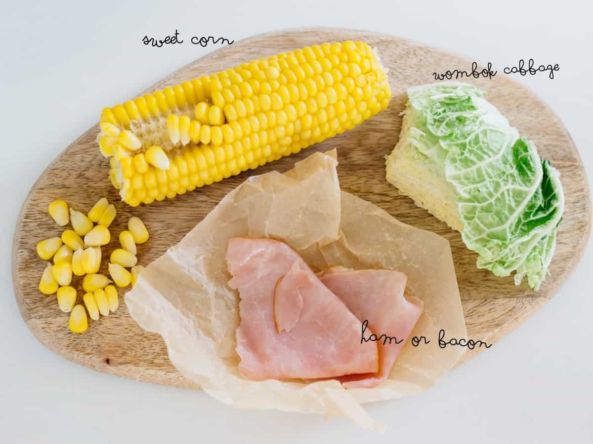 sweet corn, napa cabbage, ham on a chopping board