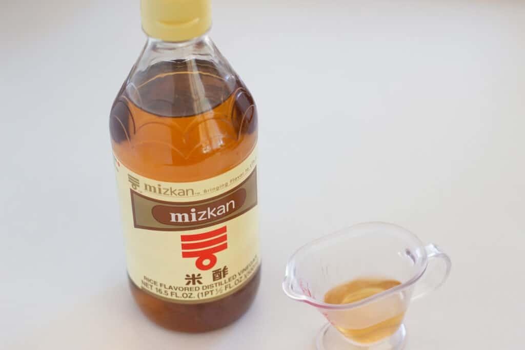 A mizkan brand rice vinegar bottle and the vinegar in a small measurement jug