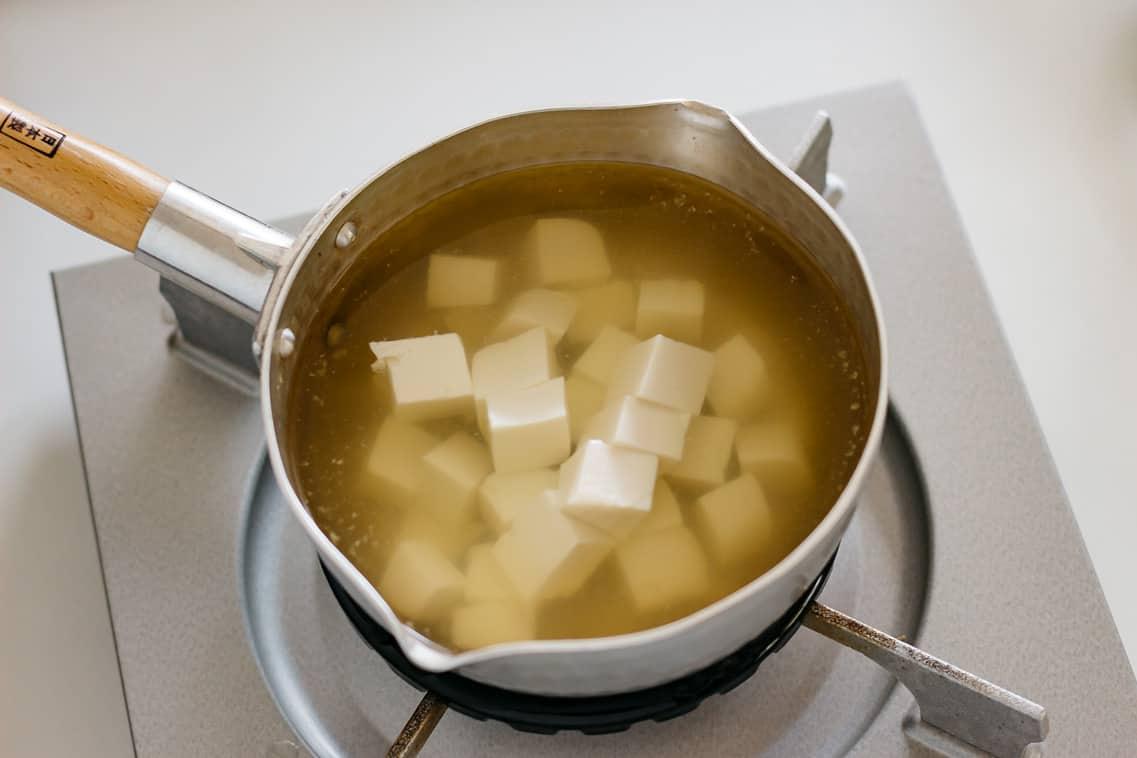 tofu added to dashi stock in a Japanese saucepan