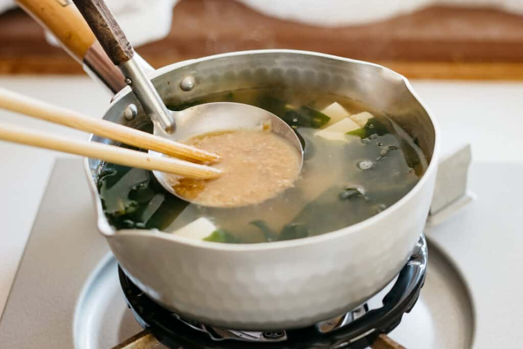 dissolving miso paste into dashi stock and ingredients in a saucepan