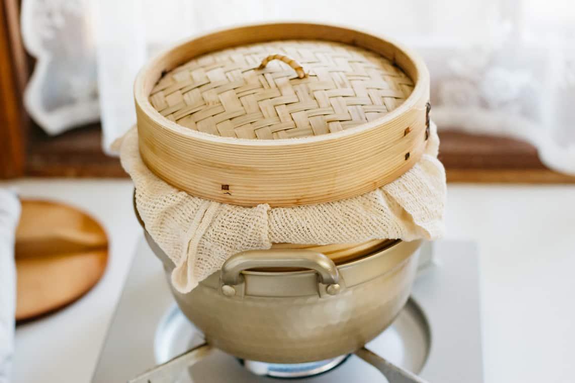 a bamboo steamer over a pot.