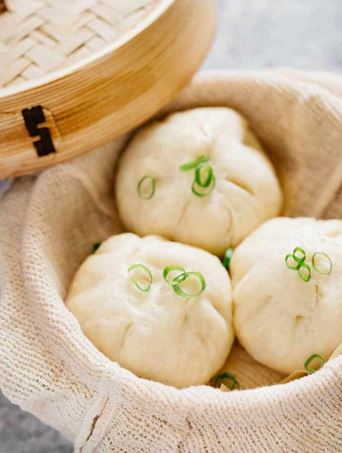 Freshly steamed three pork buns in a bamboo steamer