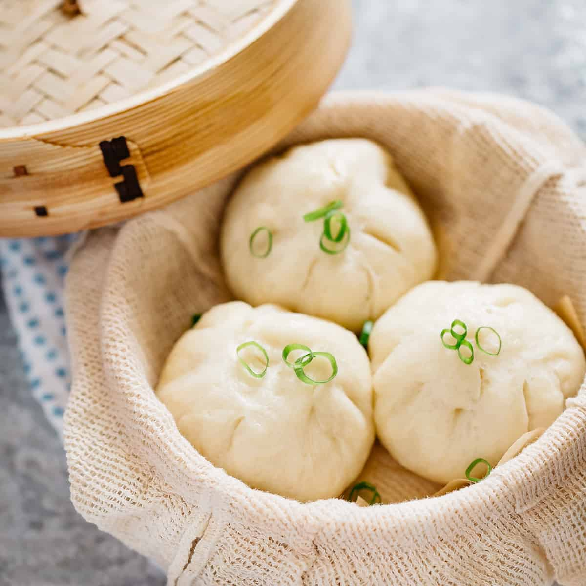 Freshly steamed three pork buns in a bamboo steamer
