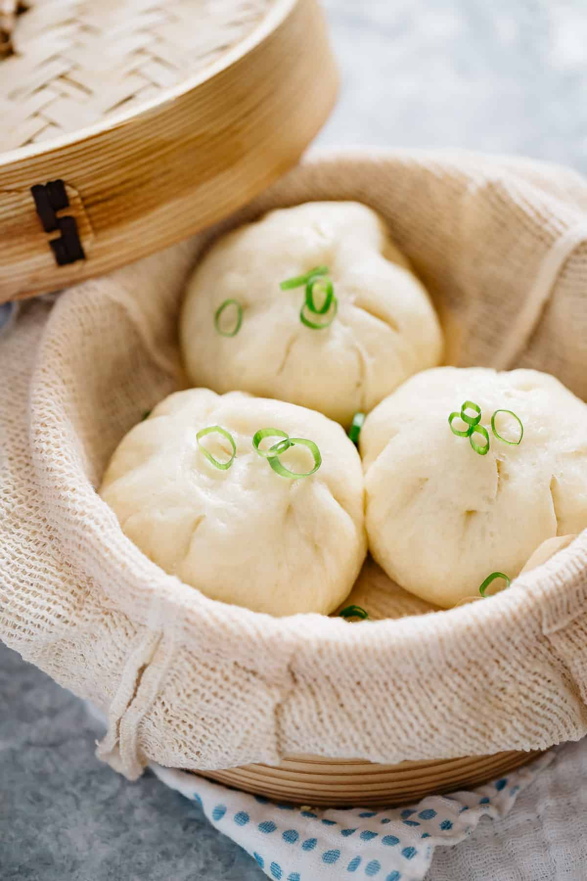 three steamed pork buns served in a bamboo steamer