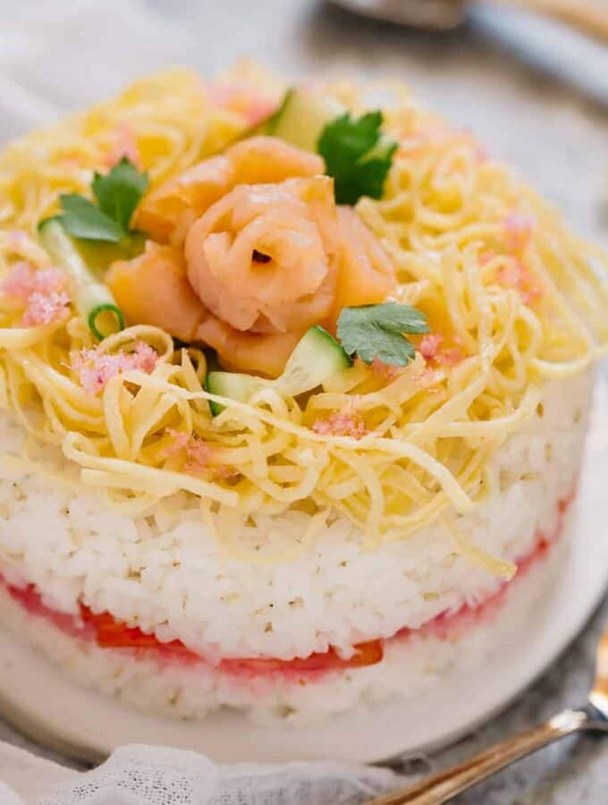 A whole sushi cake with a cake server