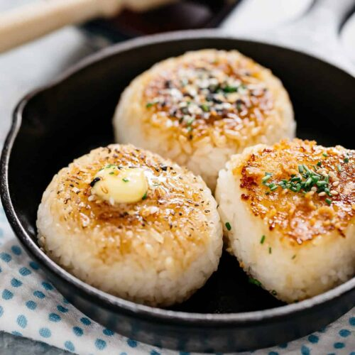 Three grilled rice balls in a cast iron skillet