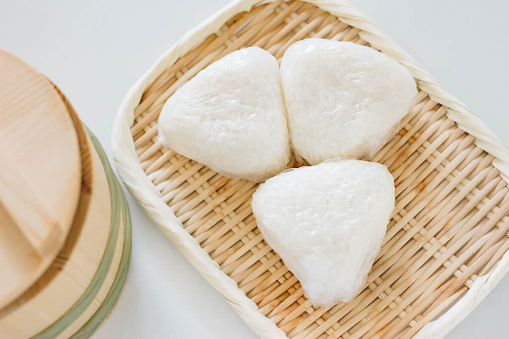 three triangle onigiri rice balls on a bamboo tray