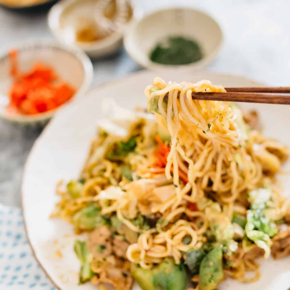 Yakisoba served on a plate, chopstick picking up noodles