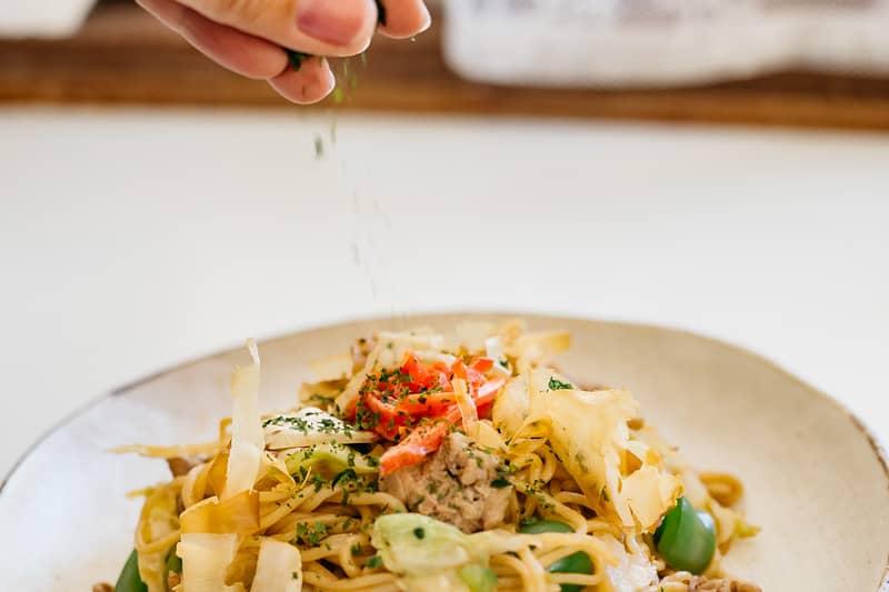 sprinkling aonori seaweed over yakisoba noodle