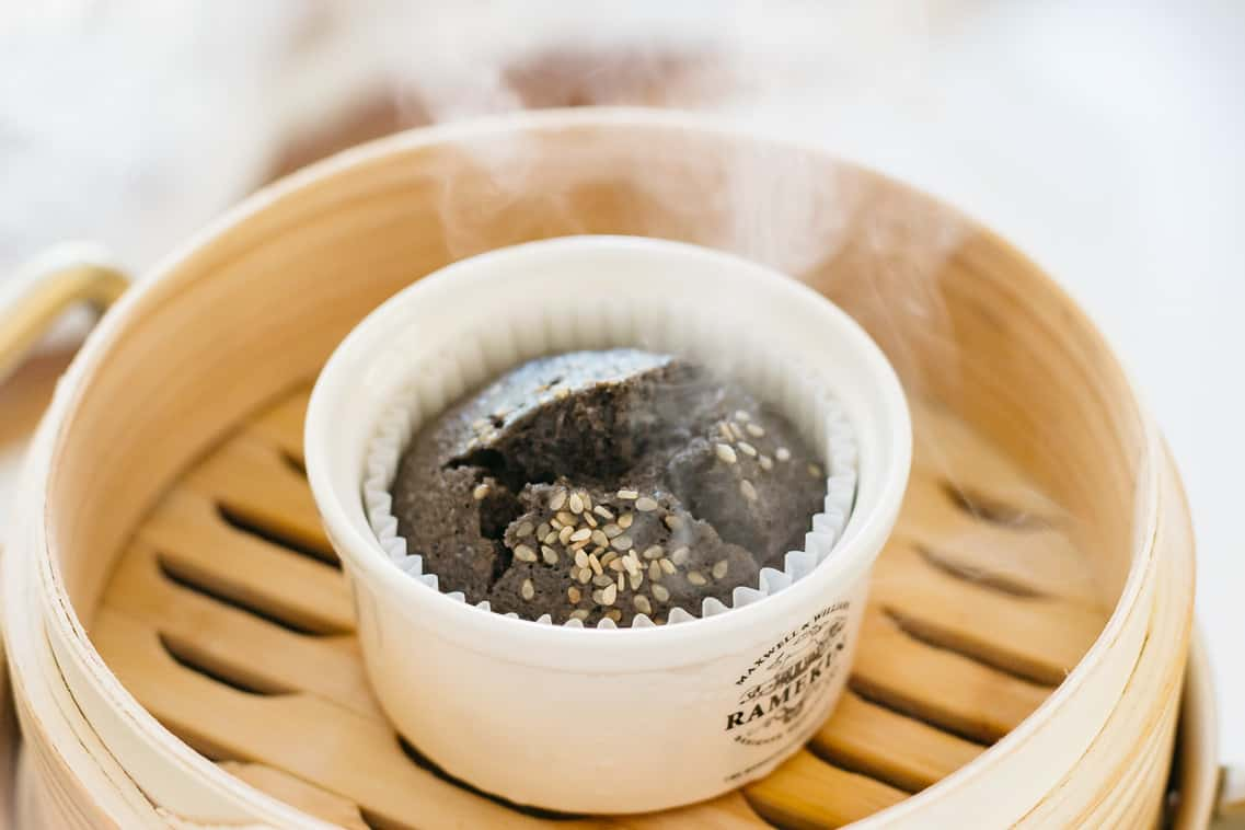one black sesame steamed buns in a bamboo steamer and steam coming out