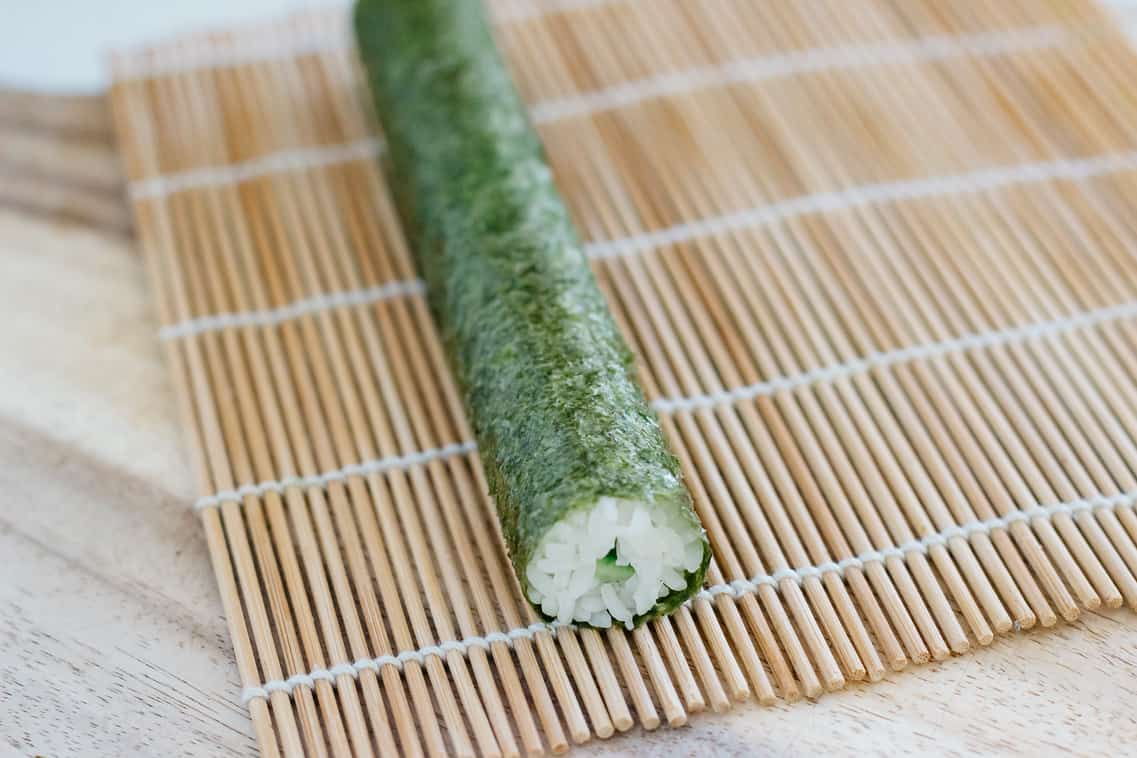 a cucumber roll on a bamboo mat