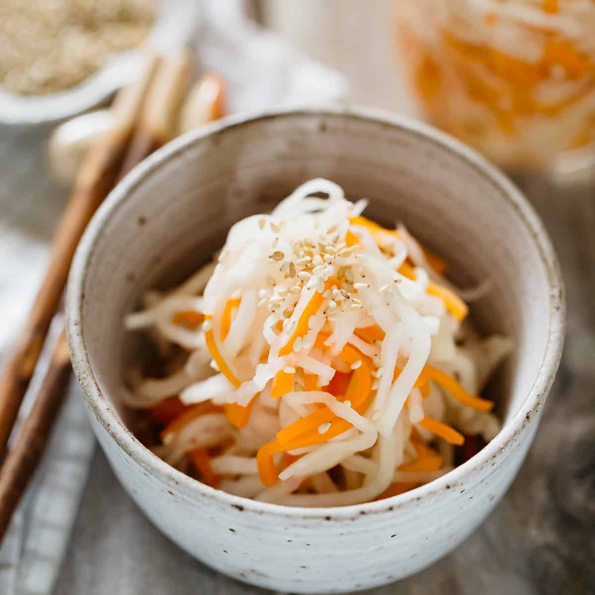 pickled daikon and carrot served in a small bowl with a pair of chopsticks