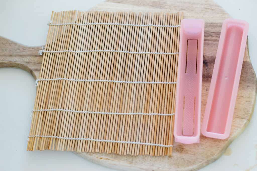 a bamboo sushi rolling mat on the left and a plastic mold on the right