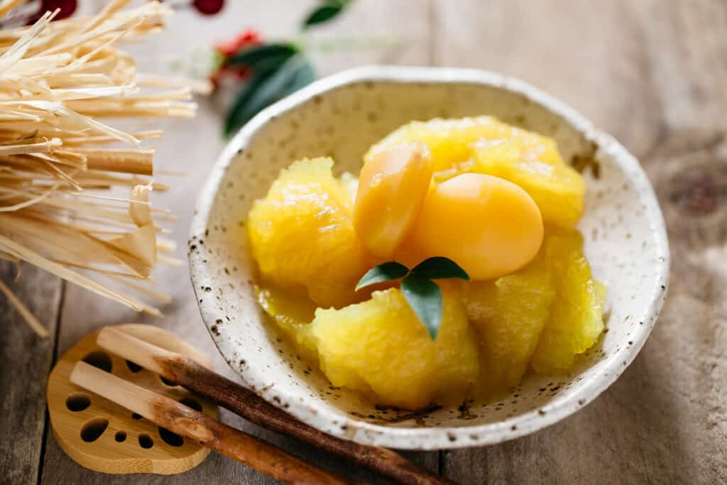Japanese sweet potato mashed and served in a small bowl with two candied chestnuts on top