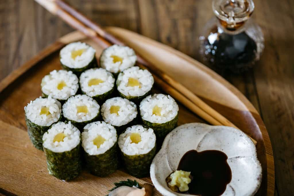 12 oshinko roll pieces served on a wooden plate with a small bowl of soy sauce and wasabi