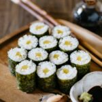 12 pieces of oshinko roll served on a wooden plate with a small bowl of soy sauce with wasabi
