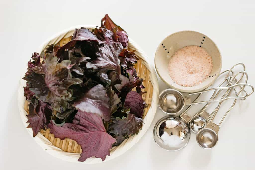 red shiso leaves on a round bamboo tray with sea salt in a small bowl