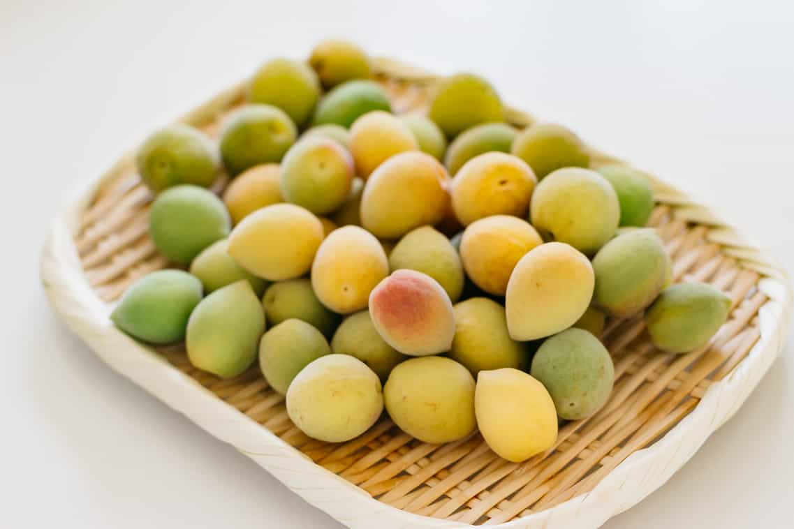 yellowish lipen ume plums on a bamboo tray