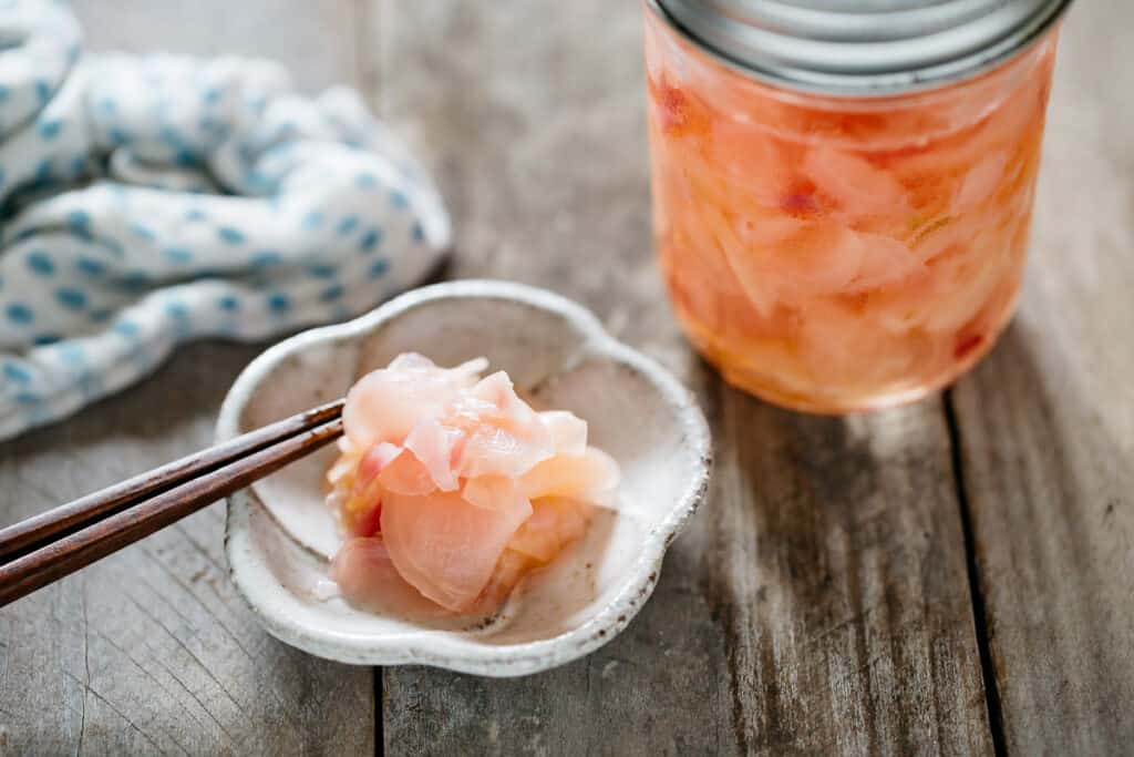 pickled ginger served on a small plate and a jar of pickled ginger