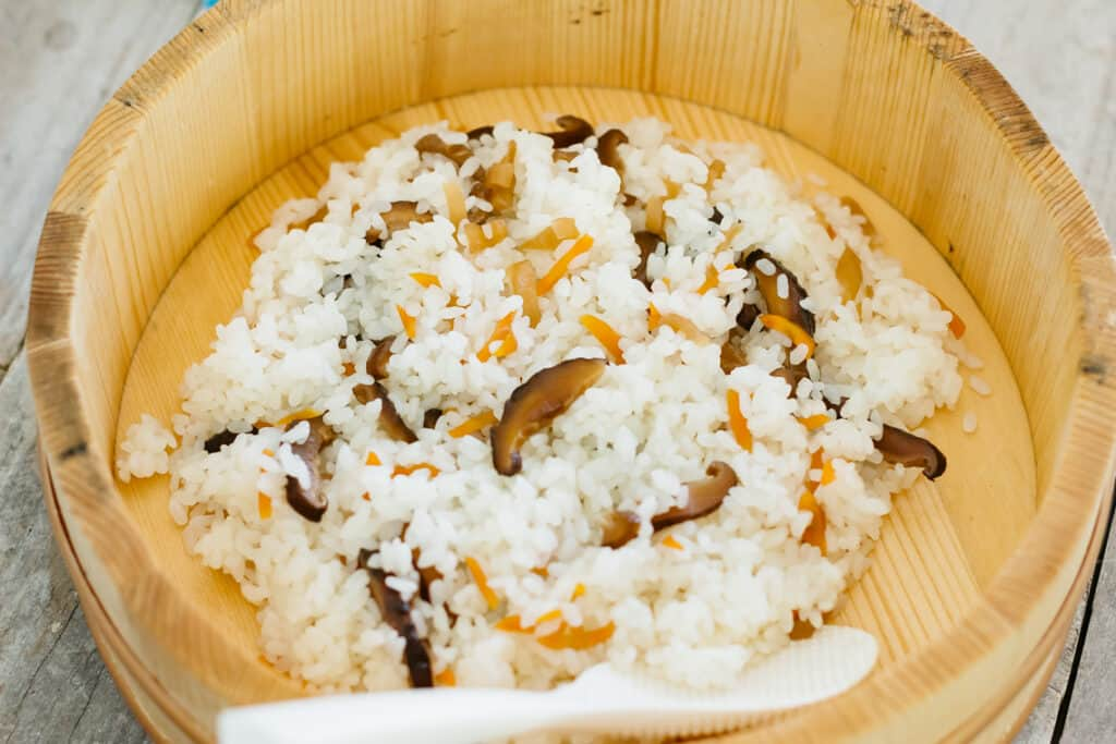 hangiri wooden tub with sushi rice in it.