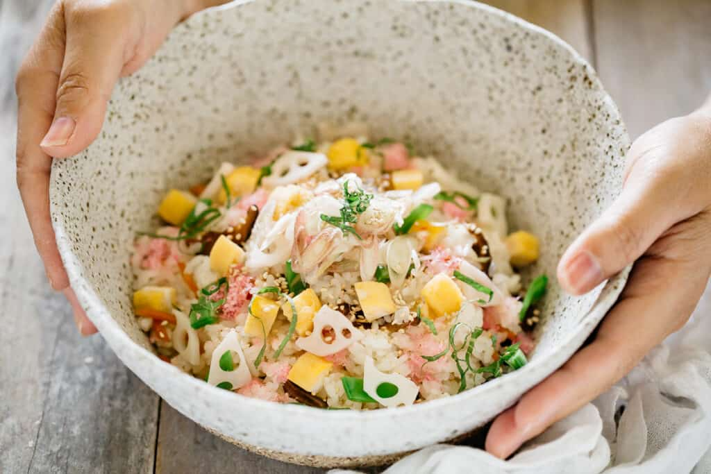 hands holding Chirashi served in a large handmade Japanese pottery bowl