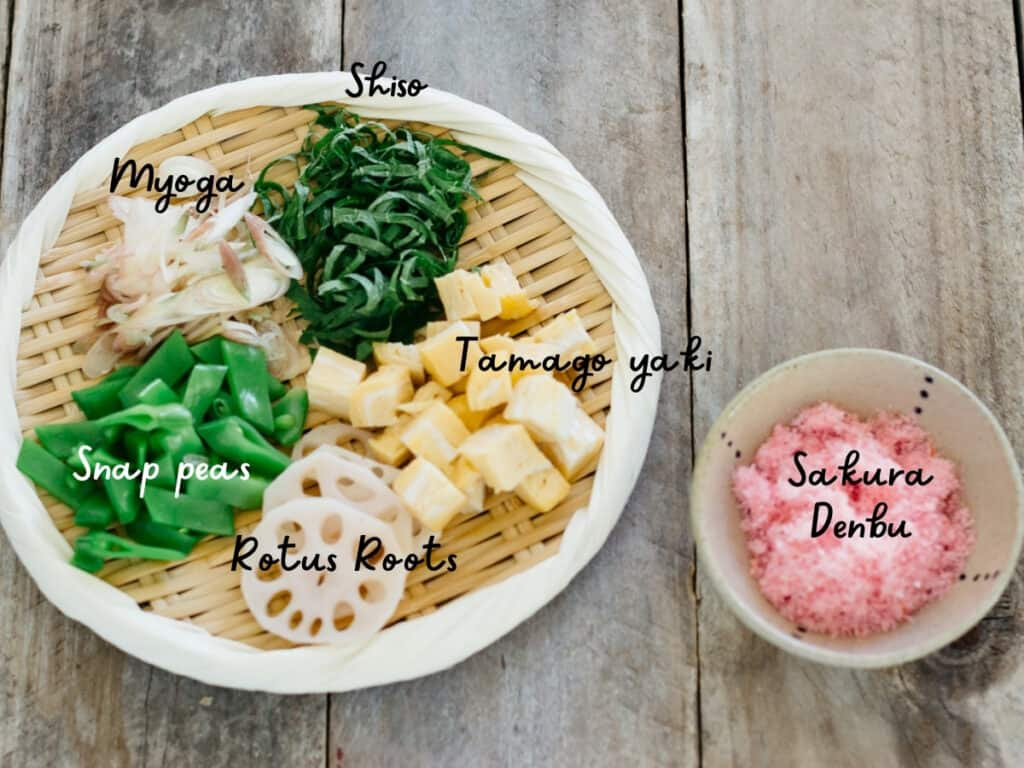 cut tamagoyaki, renkon lotus roots, snow peas, sliced myoga and chopped shiso leaves on a round bamboo tray and sakura denbu in a small bowl