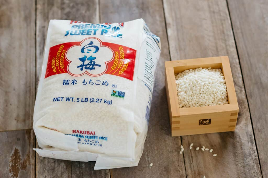 Mochigome packet on the left and rice grains in a wooden container on the right