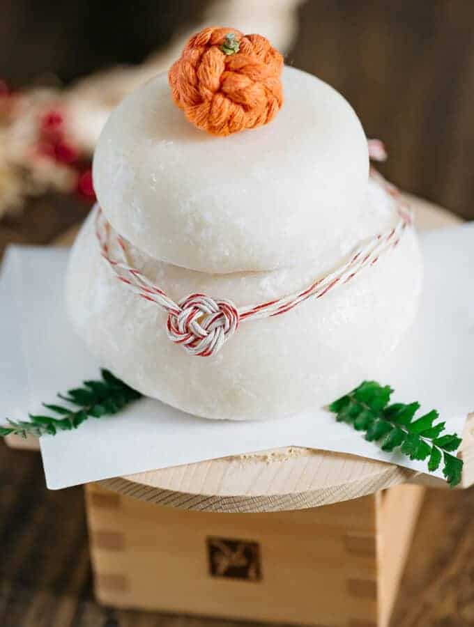 two tired kagami mochi decorated with mizuhiki and a orange ornament