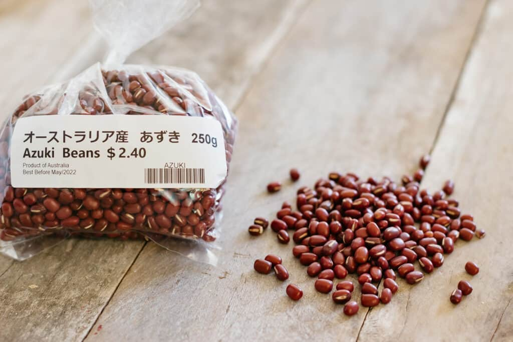 Azuki bean in a packet on the left and beans on the bench on the right