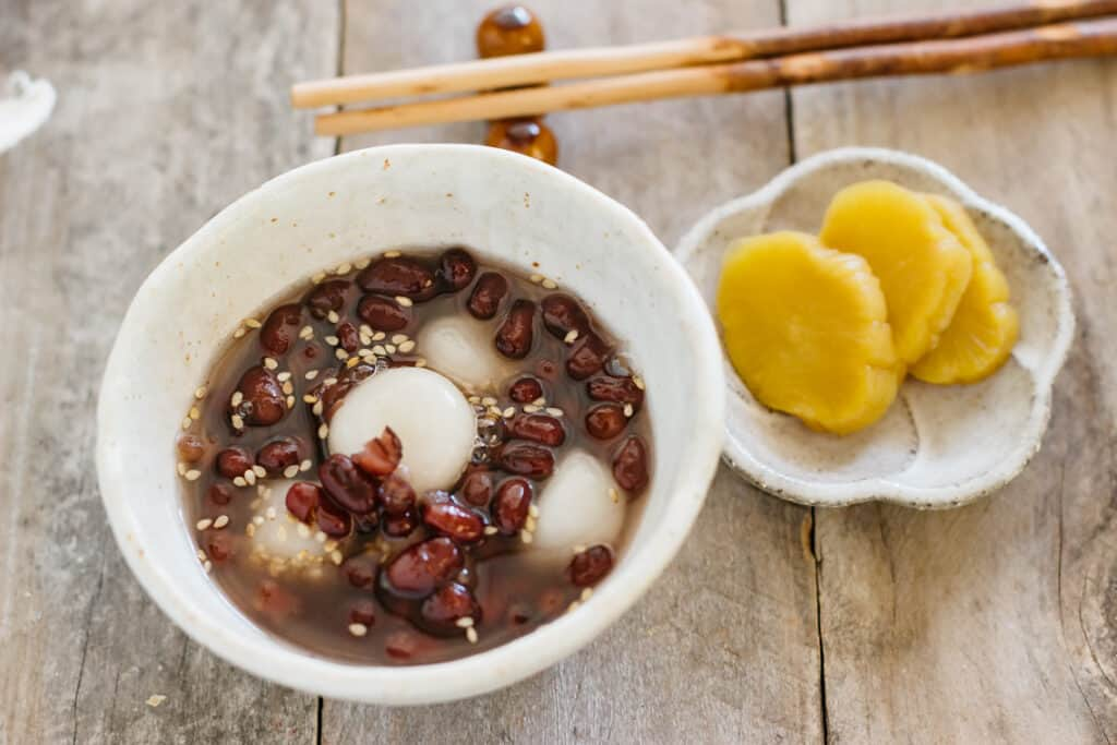 Red bean soup served in a small bowl with a small plate of pickled daikon