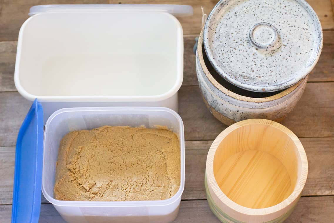 a rectangle enamel container, a rectangle plastic container, round pottery, and round wooden container
