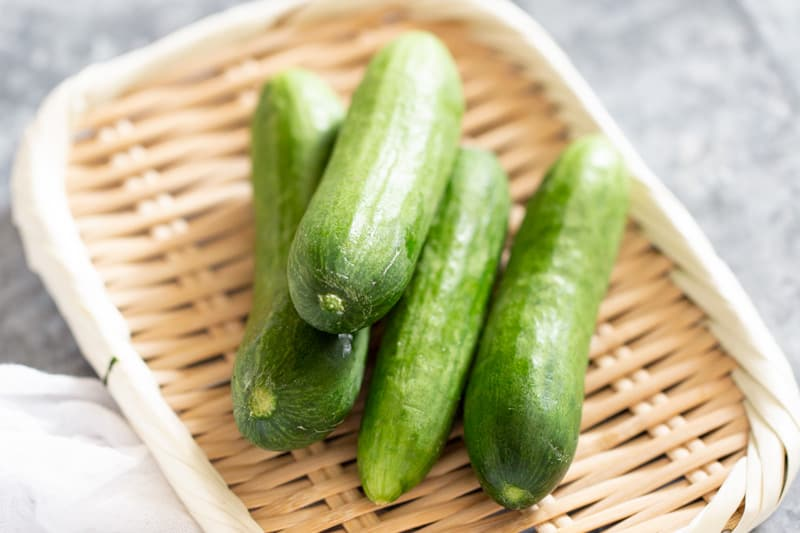 4 cucumbers on a bamboo tray