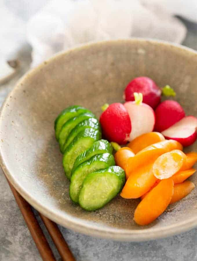 rice bran pickled cucumber, radish, and carrots tsukemono served in a round shallow bowl