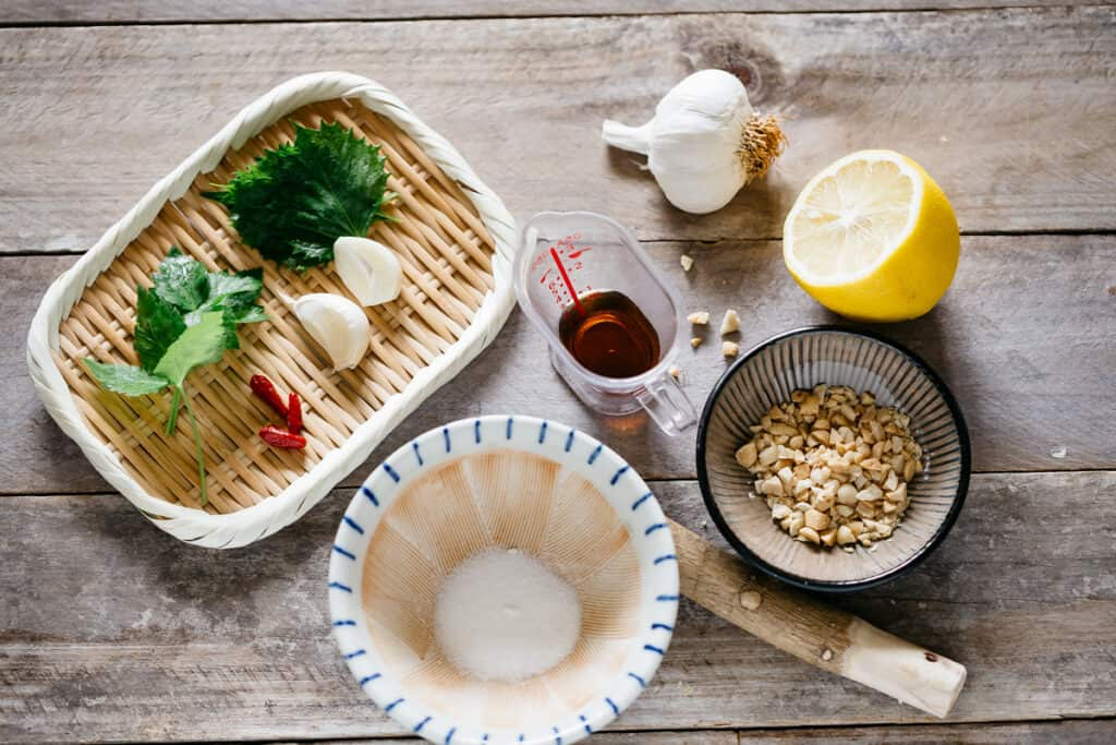 mitsuba, shiso garlic, and chili on a bamboo tray, lemon, crushed peanuts, sugar in a small mortar, and fish sauce in a small container