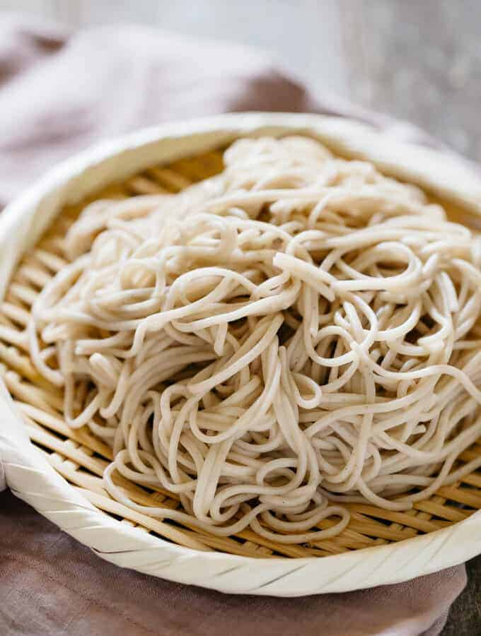 cooked soba noodles served on a bamboo tray