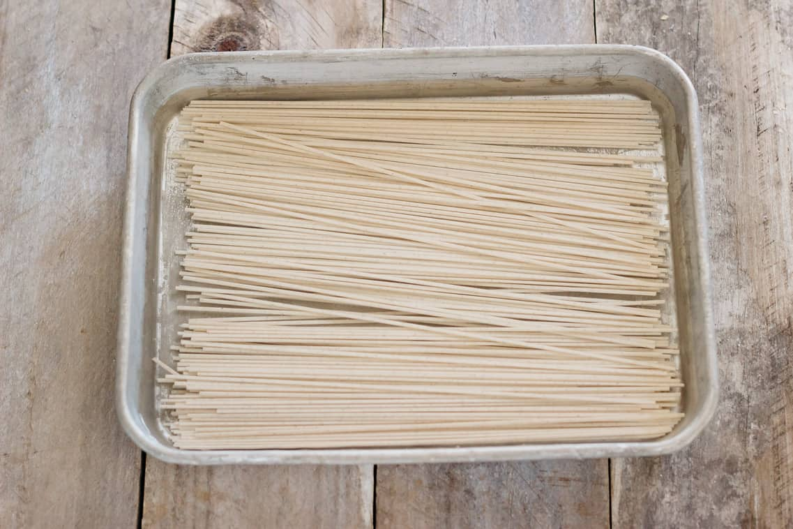 soba noodles are being soaked in a shallow tray